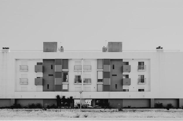 Современный дом с балконами и окнами в черном и белом с растениями и деревьями перед