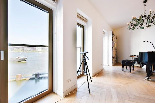 망원경이 달린 책장과 피아노가 비치 된 도시 채널을 볼 수있는 탁 트인 창문이있는 현대 주택