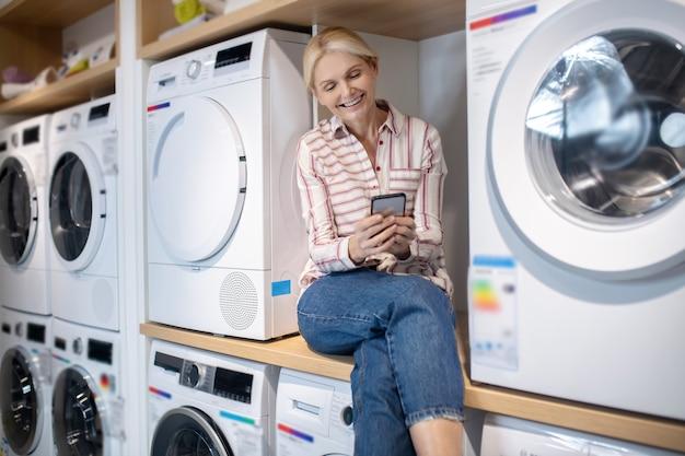 현대 주부. 손에 스마트 폰으로 세탁기에 앉아 스트라이프 셔츠에 금발 여자
