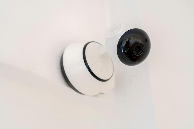 벽에 설치된 현대적인 실내 홈 보안 또는 감시 카메라. 홈 보안 개념, 원격 감시, 감시.