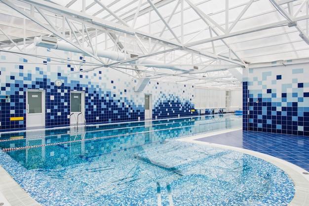 Современный крытый светлый бассейн, украшенный синей плиткой