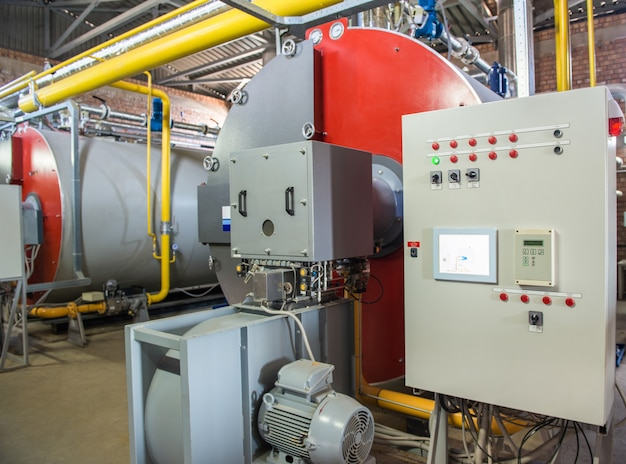 コンプレッサー設備を備えた近代的な工業用ボイラー室。コントロールパネル