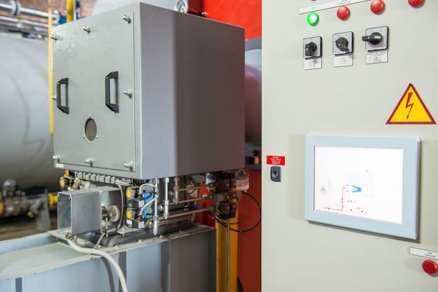 コンプレッサー設備を備えた近代的な工業用ボイラー室。コントロールパネル Premium写真