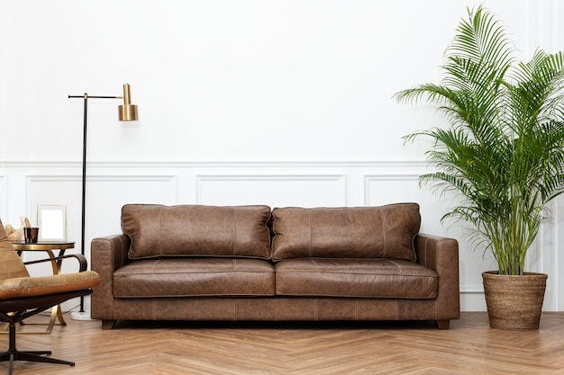 Modern industrial luxury style living room interior with leather couch, golden lamp, and houseplants