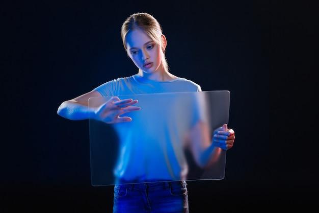 현대적인 혁신. 그것을 누르는 동안 투명 스크린을 들고 심각한 젊은 여자