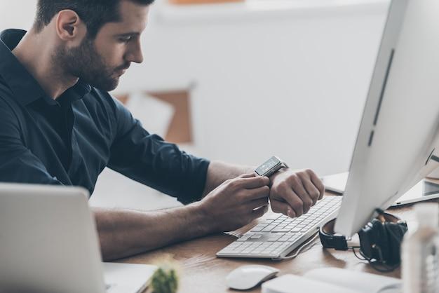 현대 혁신. 창의적인 사무실에서 책상에 앉아있는 동안 스마트 시계를 설정하는 잘 생긴 젊은 남자