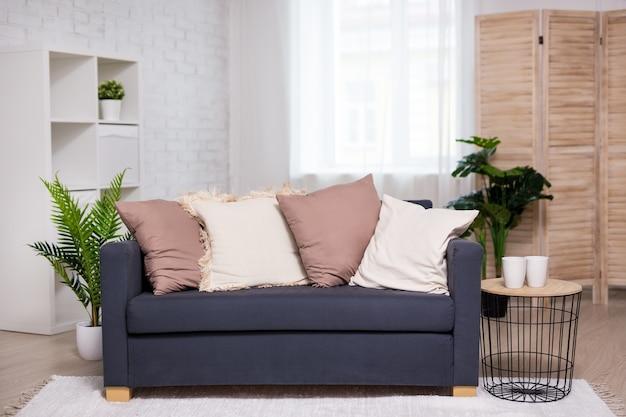 モダンなインテリア-ソファ、枕、植物、屏風のある明るいリビングルーム