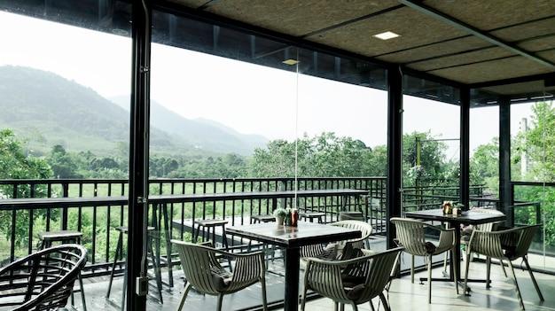 Современный интерьер, стул и столик в кафе-ресторане с зеленой природой, тихая и прохладная атмосфера по утрам, комната со стеклянными окнами выходит окнами на природу