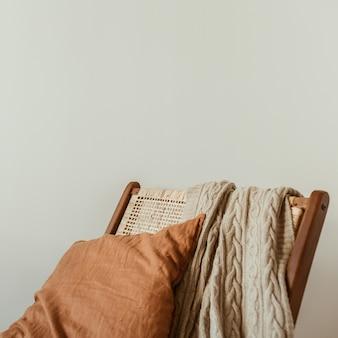 현대적인 인테리어 디자인 개념. 세련된 등나무 나무 의자, 니트 체크 무늬, 생강 베개