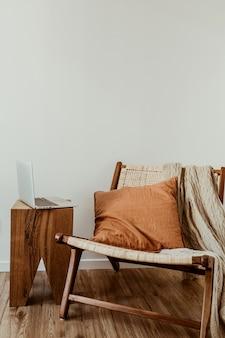 Современная концепция дизайна интерьера. стильное деревянное кресло из ротанга, вязаный плед, имбирная подушка