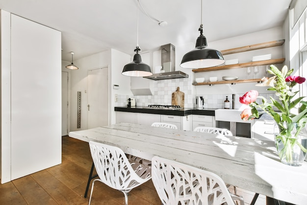 Modern interior design of cozy dining zone with table and chairs illuminated by hanging lamp in studio apartment