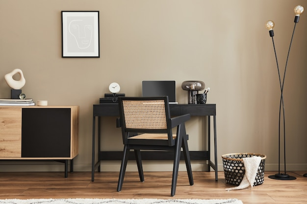 Modern interior design of home office space with stylish chair, desk, commode, black mock up poster frame, lapatop, book, office supply and elegant presonal accessories in home decor