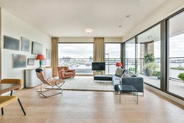 大きな窓のあるラウンジゾーンに快適なソファと柔らかいカーペットを備えた現代的なオープンスペースのアパートのモダンなインテリアデザイン