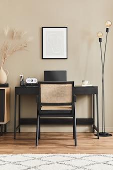 Современный дизайн интерьера домашнего офиса со стильным стулом, столом, комодом, черной рамой, лаптопом, книгой, канцелярскими принадлежностями и элегантными личными аксессуарами в домашнем декоре.