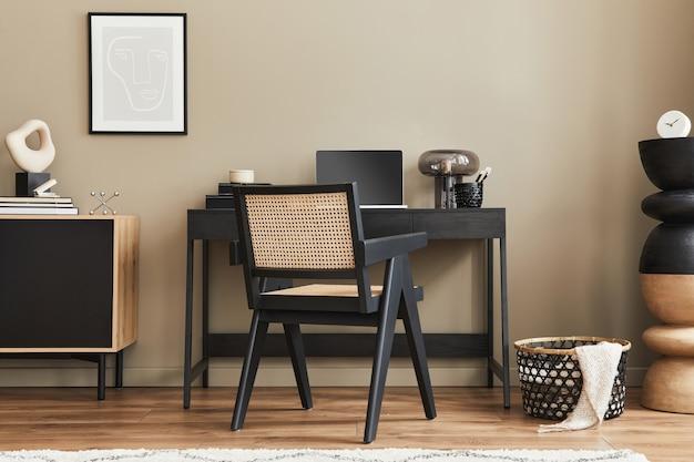 Современный дизайн интерьера домашнего офиса со стильным стулом, столом, комодом, черной рамкой для макета плаката, ноутбуком, книгой, офисным органайзером и элегантными личными аксессуарами в домашнем декоре. шаблон.