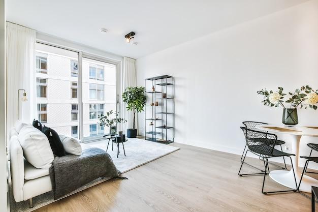 白い壁の広々としたアパートのカーペットの上に置かれたクッションと装飾的なテーブルを備えたライトグレーの柔らかい家具を備えたラウンジゾーンのモダンなインテリアデザイン