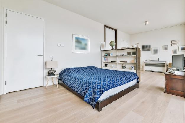 흰 벽이있는 방에 장식 용품이있는 선반 근처에 침대가있는 열린 공간 집의 현대적인 인테리어 디자인