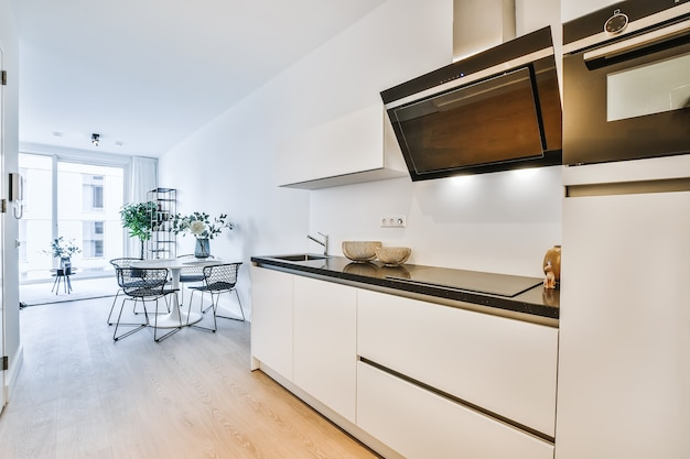 白と黒の色調の家具や電化製品を備えた珍しい幾何学的形状の小さな家庭用キッチンのモダンなインテリアデザイン