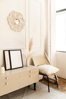 モダンなインテリアデザイン。快適な箪笥、椅子、自家植物、絵画、カーペット、白い壁で飾られたスタイリッシュで明るいリビングルーム。