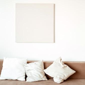 현대적인 인테리어 디자인. 편안한 소파, 베개, 그림, 흰색 벽으로 장식 된 세련되고 밝은 거실