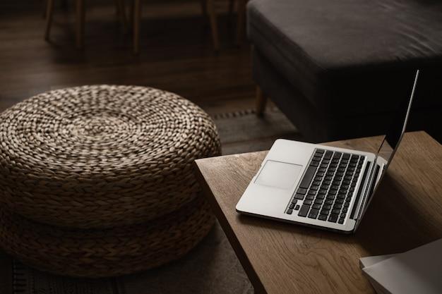 モダンなインテリアデザイン。無垢材のテーブル、籐のプーフ、ラップトップコンピューターで飾られたスタイリッシュな明るいリビングルーム