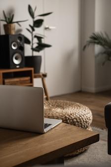 モダンなインテリアデザイン。無垢材のテーブル、籐のプーフ、ラップトップコンピューター、ステレオシステムで飾られたスタイリッシュなリビングルーム。