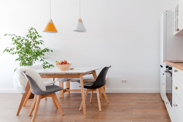 Modern interior of dining room, white furniture, lamps above wooden table, chairs, apples, bowl