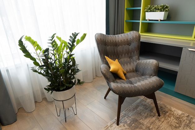 중립적 인 색상의 현대적인 인테리어. 기하학적 안락 의자, 작업 공간, 화분. 소년 또는 십대를위한 어린이 방