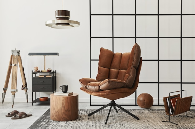 Modern interior of living room with design brown armchair, side table, pendatn lamp, loft wall, slippers, carpet, decoration and elegant personal accessories in home decor..