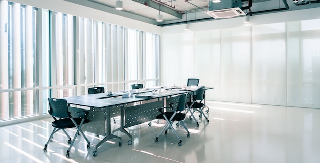 Modern interior meeting room of marketing office with evening sunset, empty large loft style conference space with chairs and tables furniture and clean glass windows