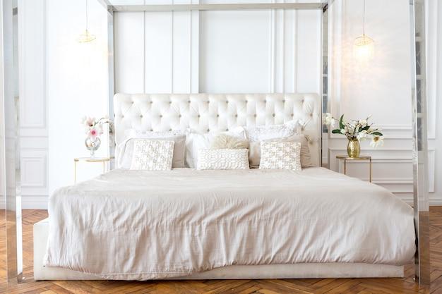 Современный интерьер роскошной большой светлой спальни.