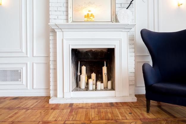 고급스러운 대형 밝은 거실의 현대적인 인테리어. 흰색 값 비싼 소파와 나무 선반, 몰딩이있는 흰색 벽과 고급스러운 샹들리에