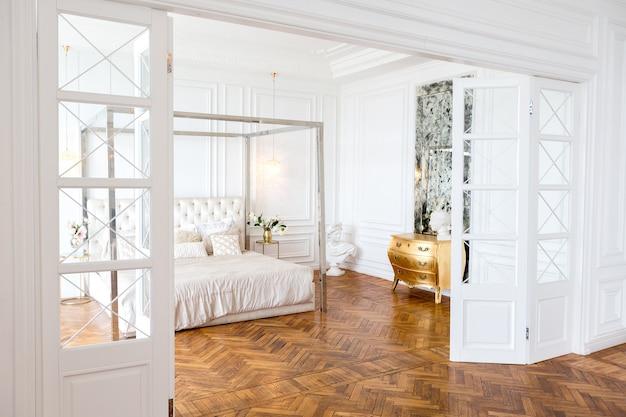 Современный интерьер роскошной большой светлой двухкомнатной квартиры. белые стены, роскошная дорогая мебель, паркет и белые межкомнатные двери
