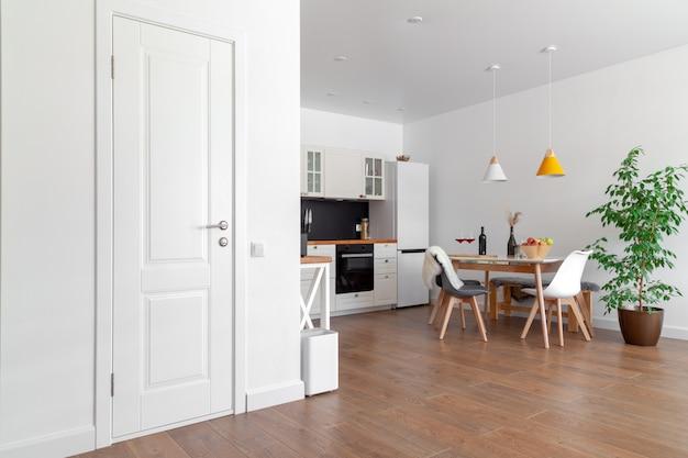 Современный интерьер кухни, белая стена, деревянные стулья, зеленый цветок в горшке. концептуальный скандинавский дизайн