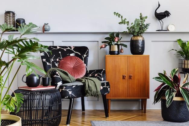 デザインアームチェア、棚付きの木製パネル、たくさんの植物、コーヒーテーブル、灰色の壁、装飾、カーペット、家の装飾の装飾用アクセサリーを備えたリビングルームのモダンなインテリア。