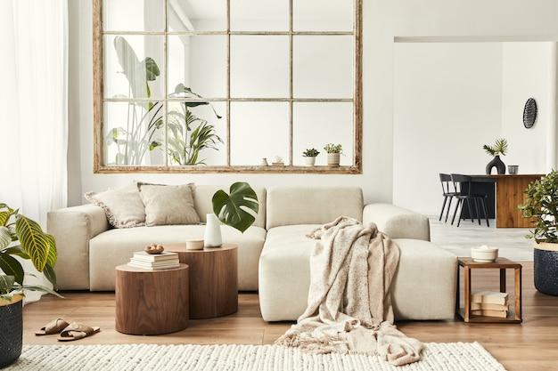 세련된 가정 장식에 디자인 모듈식 소파, 가구, 목재 커피 테이블, 격자 무늬, 베개, 열대 식물 및 우아한 개인 액세서리가 있는 개방형 공간의 현대적인 인테리어입니다. 중립 거실.