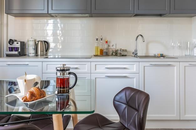 Современный интерьер светлой кухни в квартире с обеденным столом и встроенной техникой.