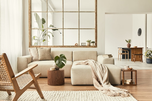 Modern interior of open space with design modular sofa, furniture, wooden coffee tables, plaid, pillows, tropical plants and elegant personal accessories in stylish home decor.