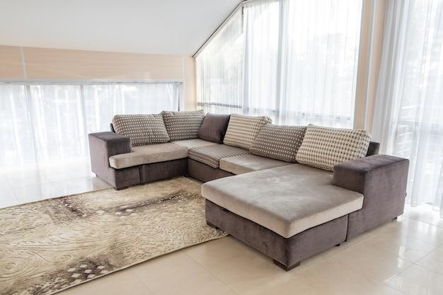 Современный интерьер с большим диваном и большими окнами