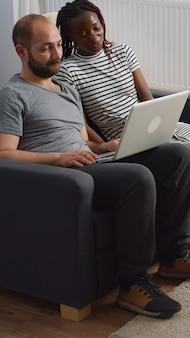 Moderna coppia interrazziale che saluta in videoconferenza