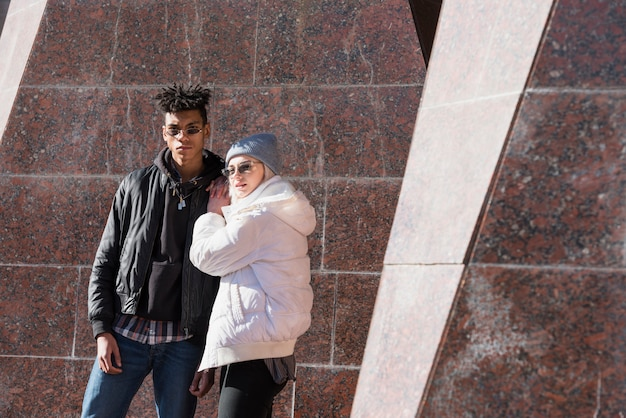 Modern interracial young couple wearing sunglasses looking at camera