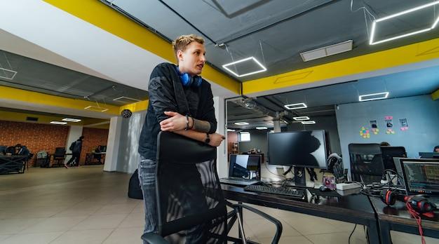 Молодой человек стоит в офисе, опираясь на стул. офис компании modern it и амбициозный разработчик, думающий о новых технологиях.
