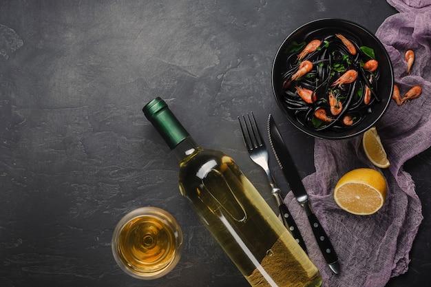 Modern italian dinner, mediterranean food, black cuttlefish ink spaghetti pasta with seafood