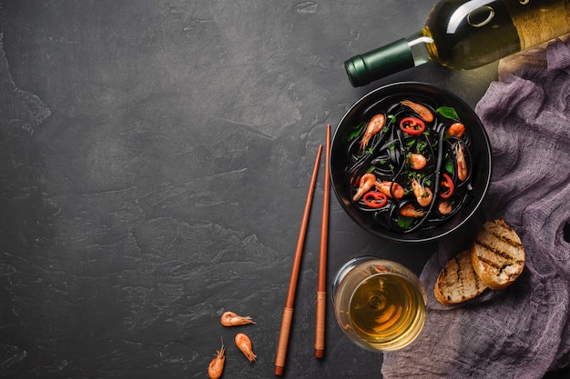 Modern japanese dinner, mediterranean food, black cuttlefish ink spaghetti pasta with seafood