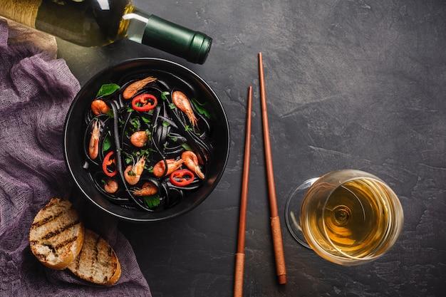 Modern japanese dinner, mediterranean food, black cuttlefish ink spaghetti pasta