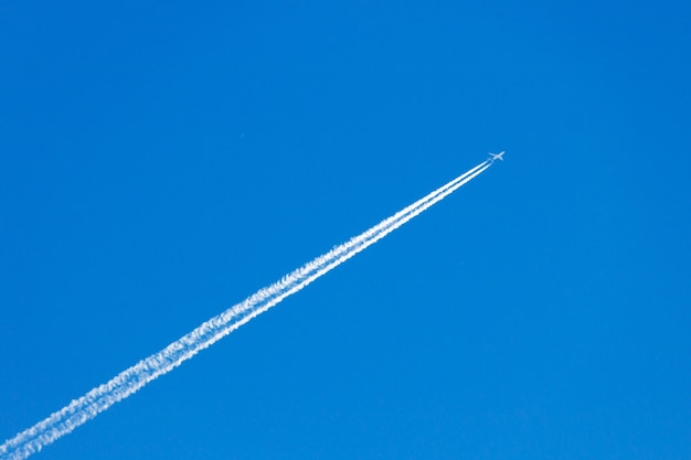Modern jet plane with white condensation track flies on a blue sky background