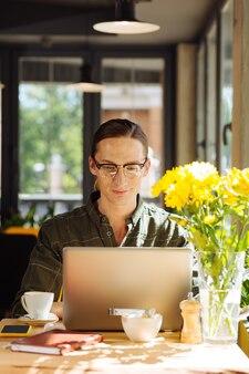 현대 직업. 프리랜서가되는 동안 자신의 노트북에서 원격으로 작업하는 긍정적 인 좋은 사람