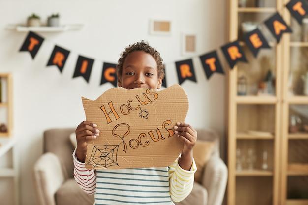 Hocus pocus 글자와 골판지를 들고 할로윈 장식 거실에 서있는 현대 즐거운 아프리카 계 미국인 소년