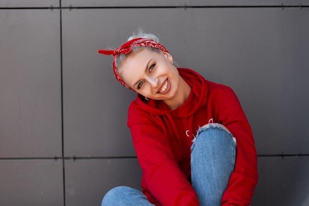 빨간 손수건과 현대적인 유행의 옷에 귀여운 미소로 현대 즐거운 젊은 여자는 따뜻한 여름날에 회색 빈티지 건물 근처에서 쉬고있다
