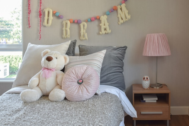 Modern kids room with doll and pillows on bed